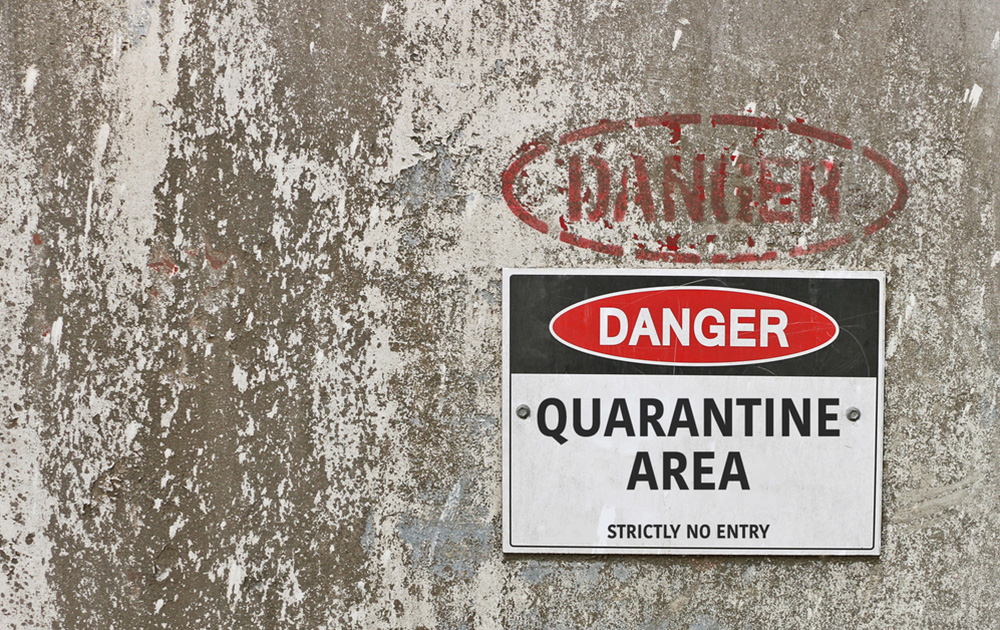 a quarantine sign on a washed out concrete wall