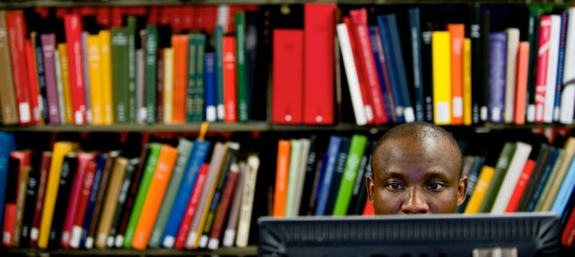 1/7/11 11:06:20 AM -- Boston, Massachusetts..Derrick Muwina, STH, surfs the web at the Mugar Library. Muwina is working towards a Doctorate in Social Ethics...Photo by Cydney Scott for Boston University Photography