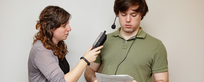 In front of a grey wall, a man with brown hair, a green shirt, and a headset is reading off of a script. A woman with brown hair, a black shirt, and a gray cardigan is holding up a device for him to read into