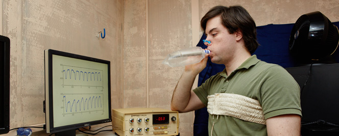 Inside a concrete booth, a man with brown hair and a green shirt wears a wrap around his chest, a blue clamp on his nose, and breathes into a water bottle. There is a respiratory device as well as a computer displaying two graphs on the desk in front of him