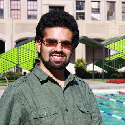 A man with black hair, a beard, sunglasses, and a green button up shirt smiles in front of an outdoor swimming pool