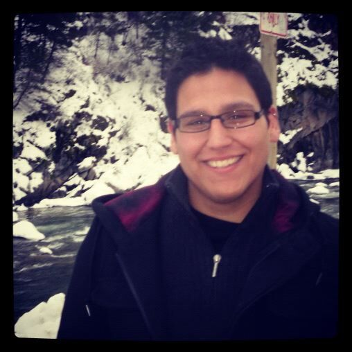 A man with black hair, glasses, and a black coat is smiling in front of a snowy mountain