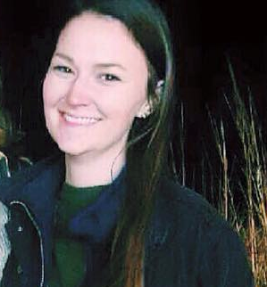 A woman with brown hair, a green shirt, and a black coat smiles outdoors