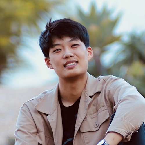 A man in a black shirt with a khaki jacket is smiling outside